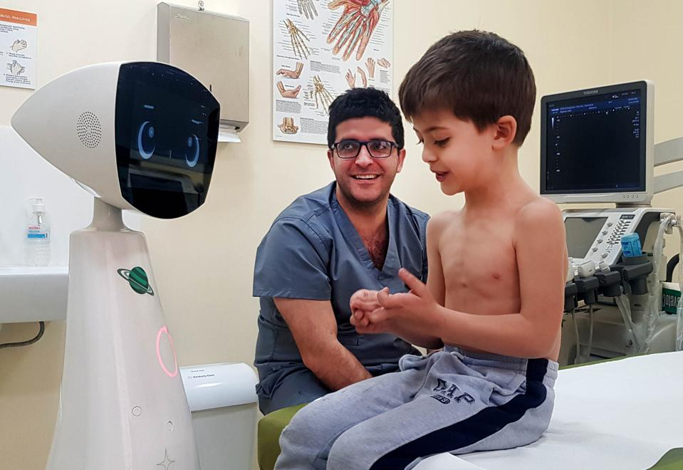 A child with Robin the Robot at a clinic in Armenia