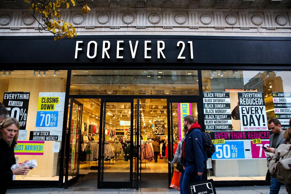 Shoppers walk past the Closing Down signs in the window of...