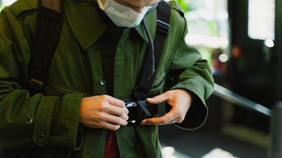 Man wearing mask puts on wearable contact tracing sensor