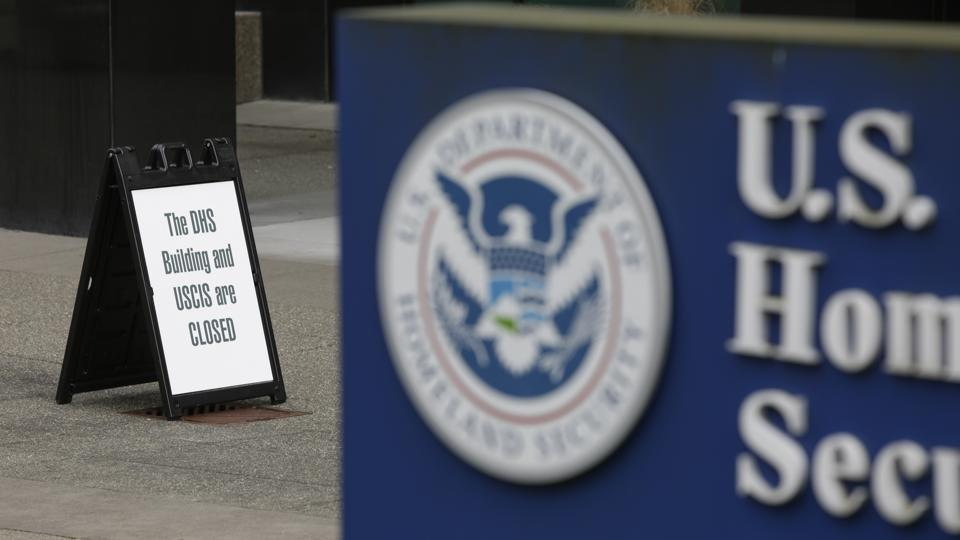 A sign outside a USCIS office indicating a closure due to the coronavirus (COVID-19) pandemic.