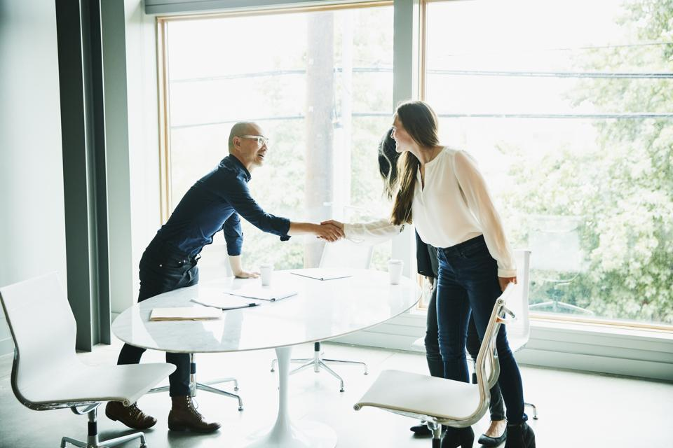 Businesswoman shaking hands with client before meeting in office conference room