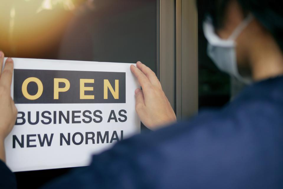 Reopening for business adapt to new normal in the novel Coronavirus COVID-19 pandemic. Rear view of business owner wearing medical mask placing open sign ″OPEN BUSINESS AS NEW NORMAL″ on front door.