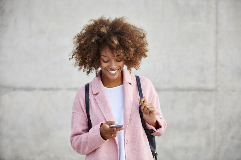 Adorable Black woman with amazing hair & sweet pink sweater checks phone. I want her life.