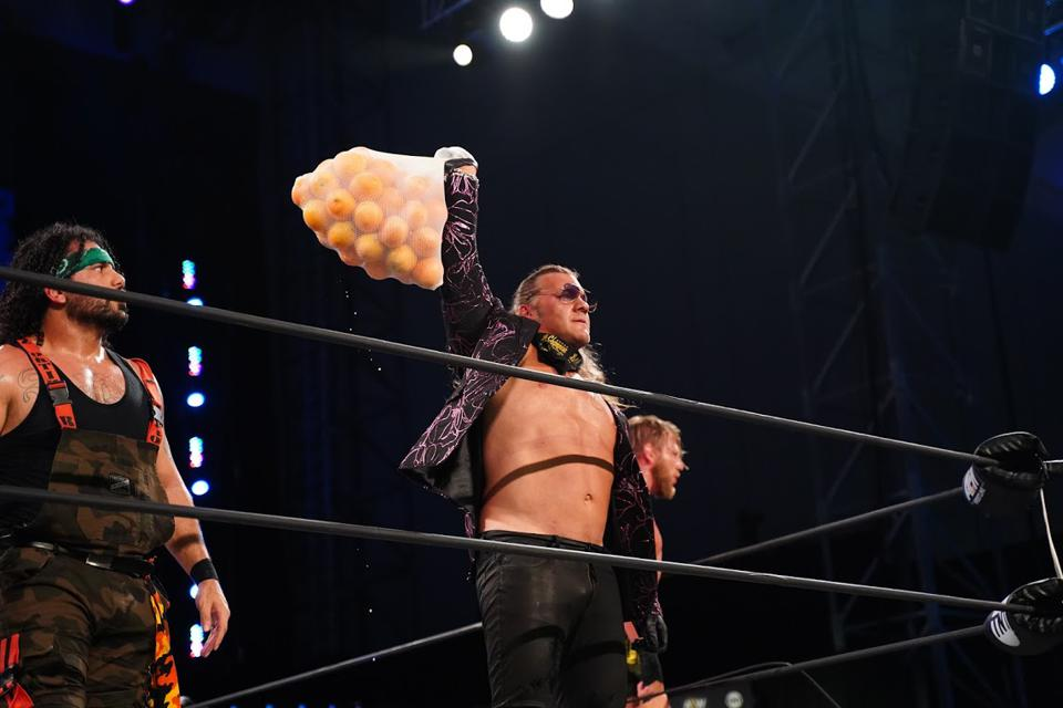 Chris Jericho brandishes a bag of oranges after using them to lay out Orange Cassidy.