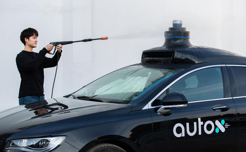 A worker tests the AutoX xFusion sensor array mounted on a vehicle by spraying water.