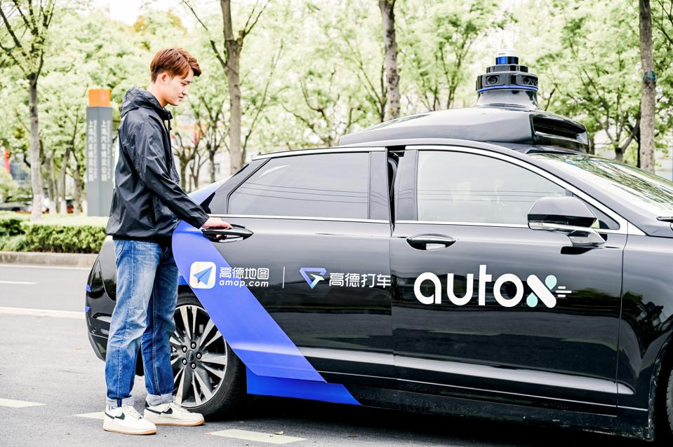 A rider enters a black AutoX self-driving car in Shanghai, China, as part of the startup's partnership with Alibaba's Amap.