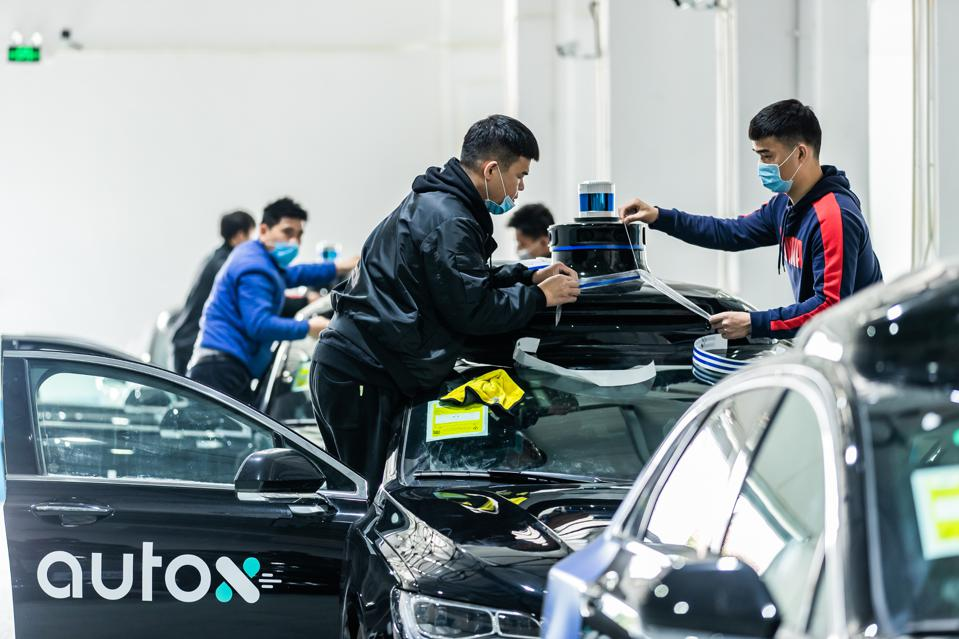 Two workers in Shanghai climb up on an AutoX sedan to install the company's xFusion sensor suite on the vehicle's roof.