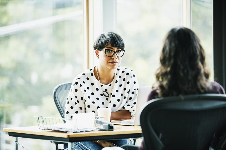 Mature businesswoman in discussion with employee while seated at workstation in office