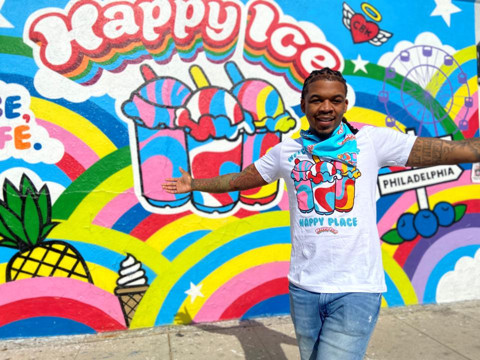 Mitchell stands in front of the colorful Happy Ice mural painted on his storefront wall.