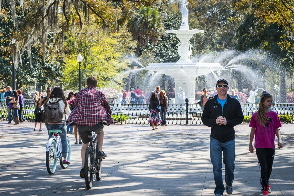 Park with large water fountain and people strolling through