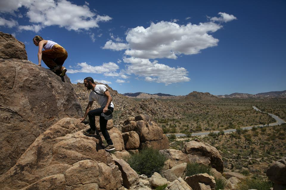 Hikers climbing over rocks in Joshua Tree National Park in California.