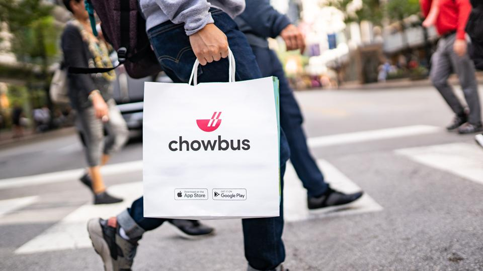 person holding chowbus bag while walking