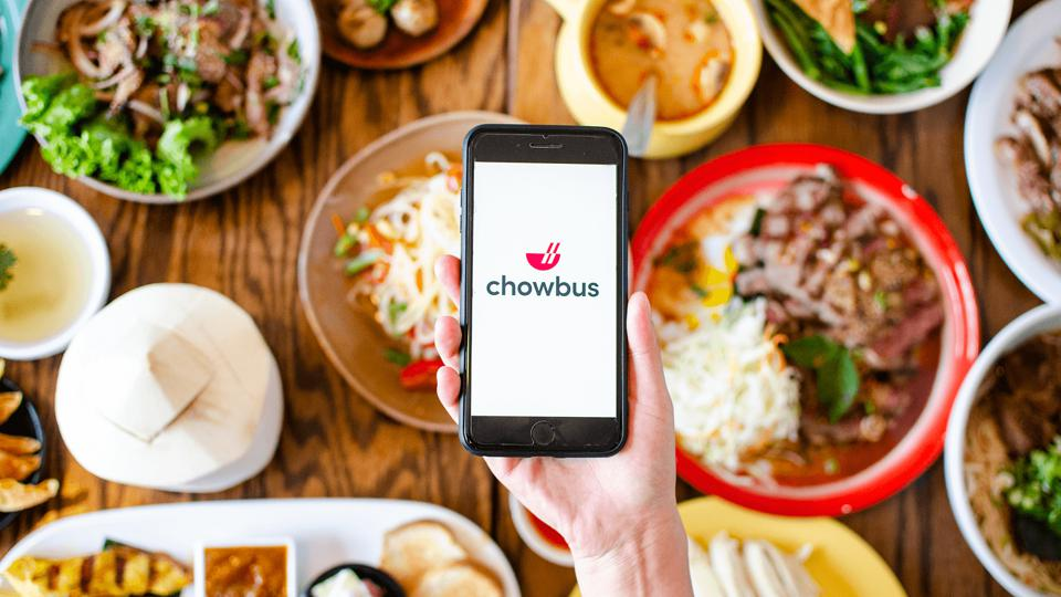 hand holding smartphone with chowbus app over table of food