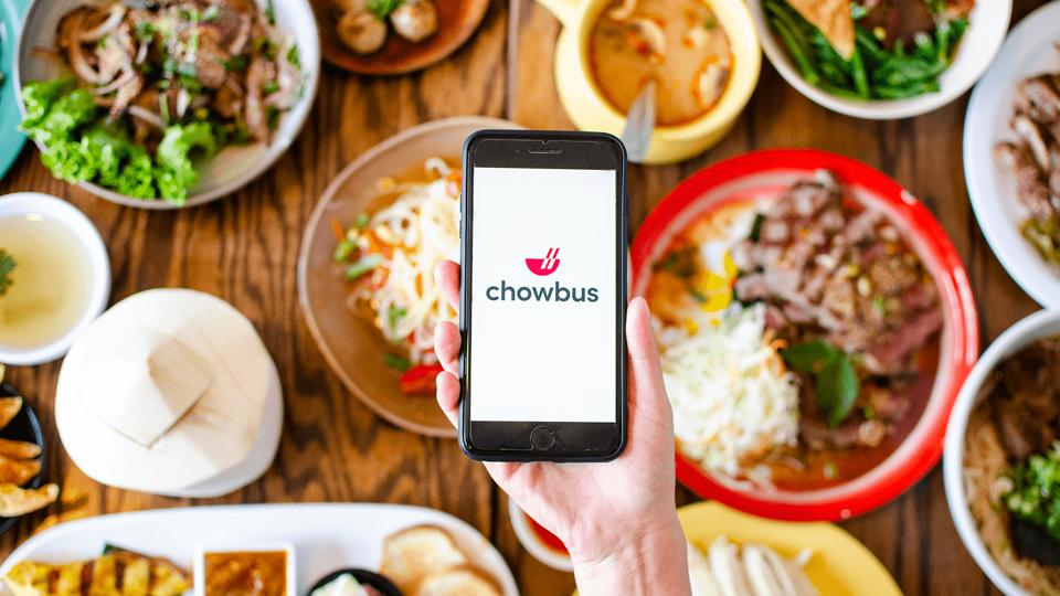 hand holding phone with chowbus app over table of food