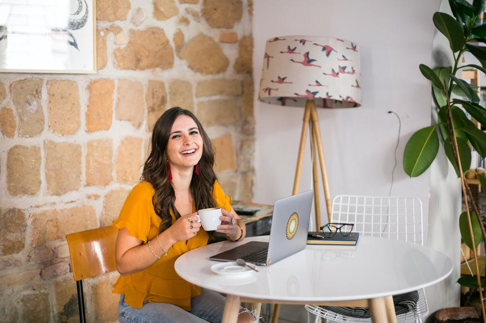 laughing businesswoman female entrepreneur brand story coach working at a coffee shop with a laptop