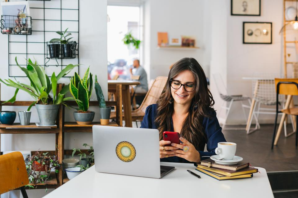 attractive businesswoman, female entrepreneur, brand story coach checking her phone and studying on her laptop while drinking coffee