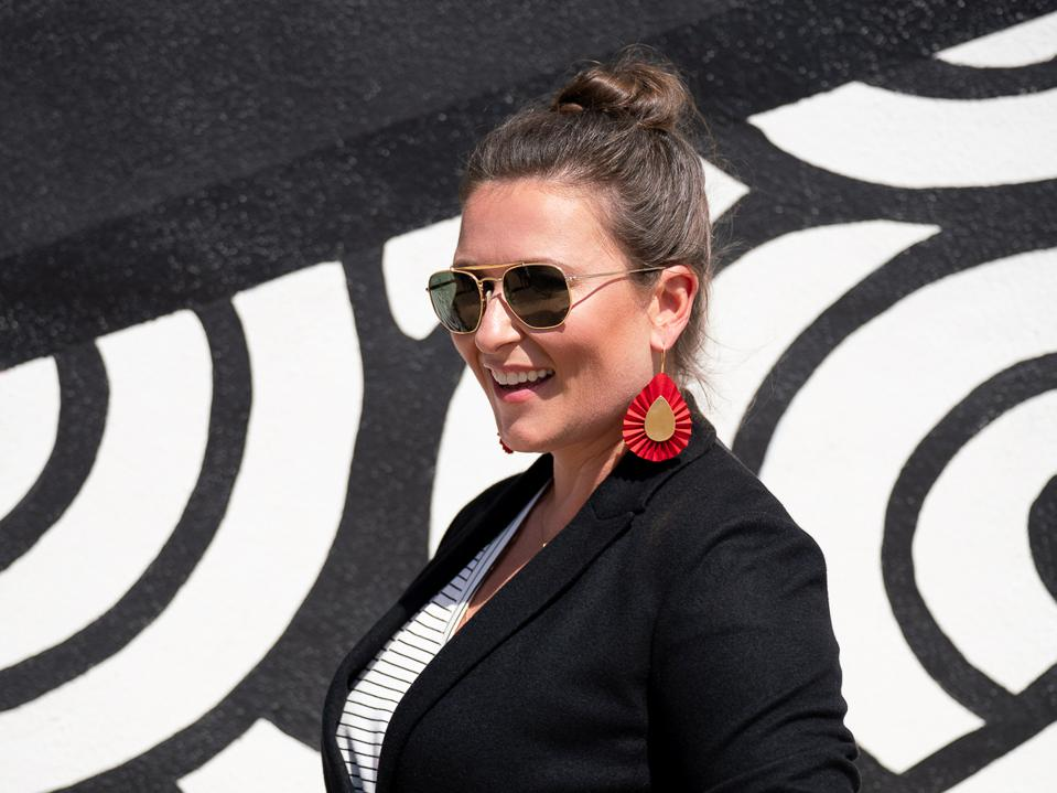 Miller, in sunglasses and Period Movement earrings, stands by a black and white wall
