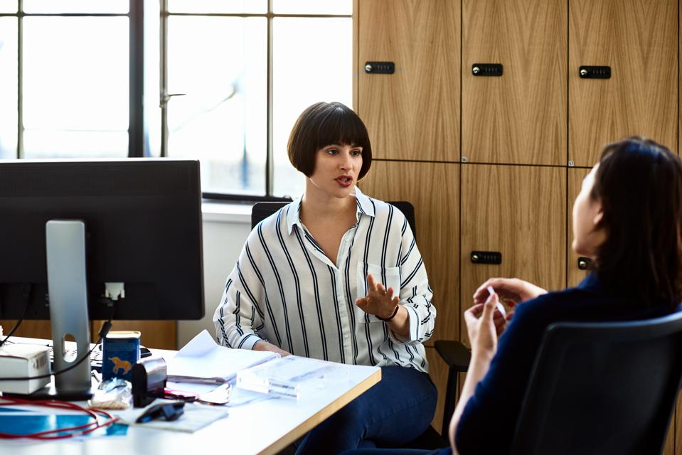 Serious businesswoman talking to colleague at desk
