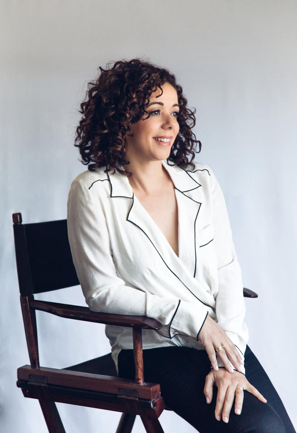 Grammy-winning vocalist Luciana Souza sitting in a chair