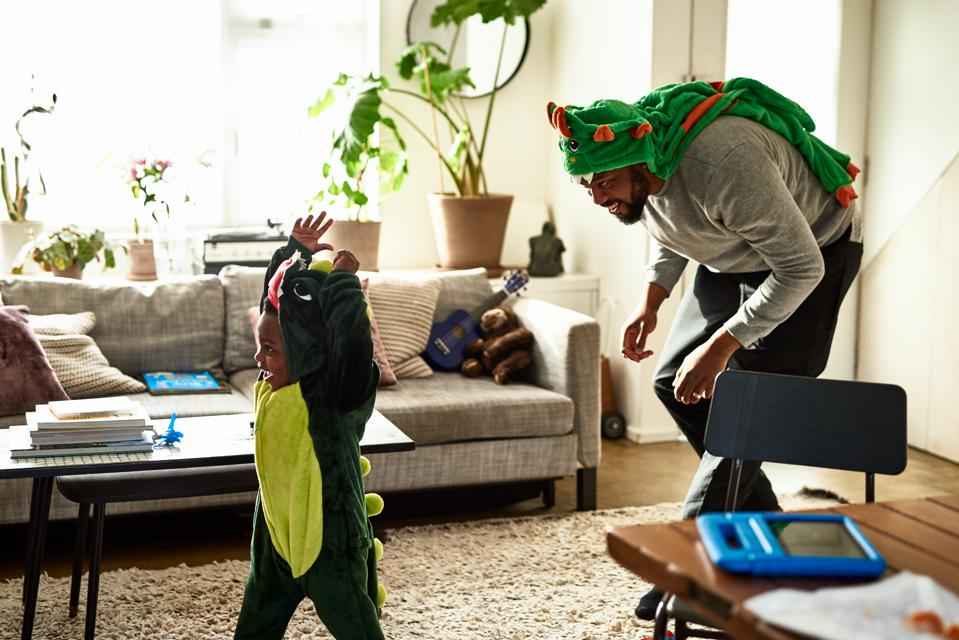 Father and son dressed as dragons playing in living room