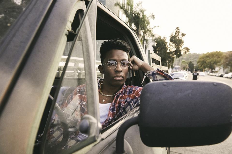 A Black young adult male with glasses in the front seat of a truck in the suburbs.