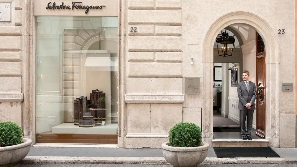 Man stands out front of Portrait Roma hotel in Rome
