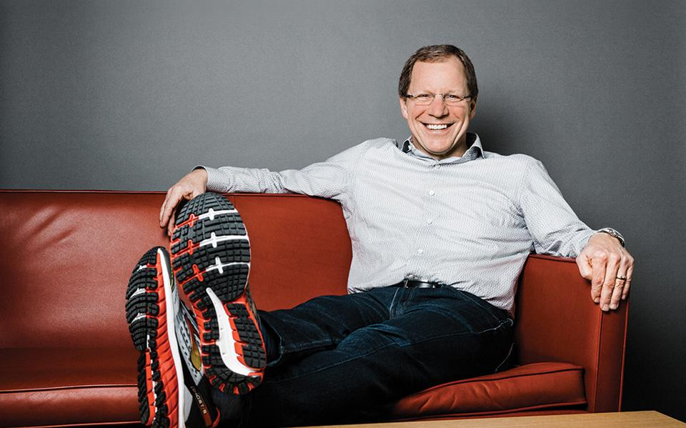 Brooks Running CEO Jim Weber sits on couch with legs crossed on table.