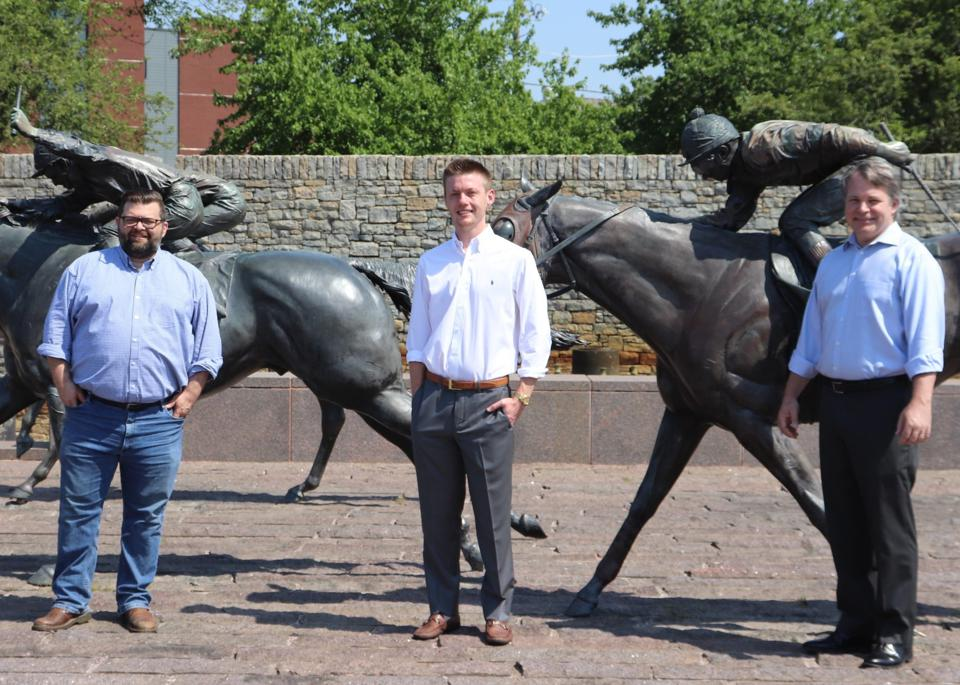 The Seats Leadership team stands in front of thoroughbred horse statues in Lexington, KY.