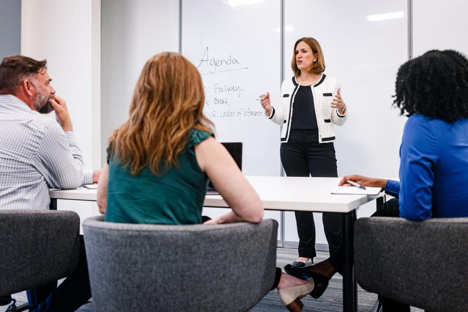 A business woman stands in front of a whiteboard as she speaks to a few people.