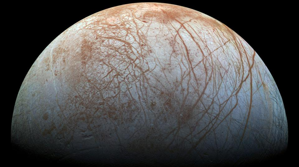 The scene shows the stunning diversity of Europa's surface geology. Long, linear cracks and ridges crisscross the surface, interrupted by regions of disrupted terrain where the surface ice crust has been broken up and re-frozen into new patterns.