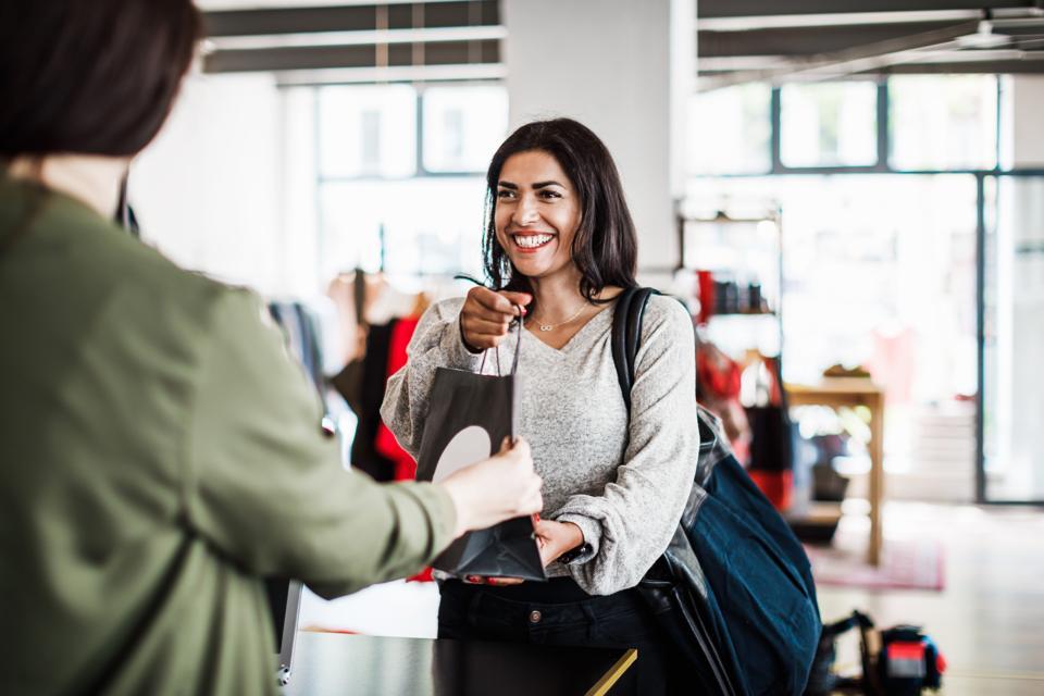 Store Clerk Handing Customer Purchased Items