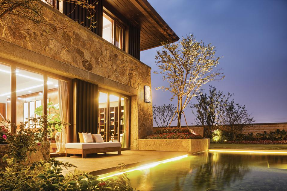 outdoor living space with pool, chaise and lighting