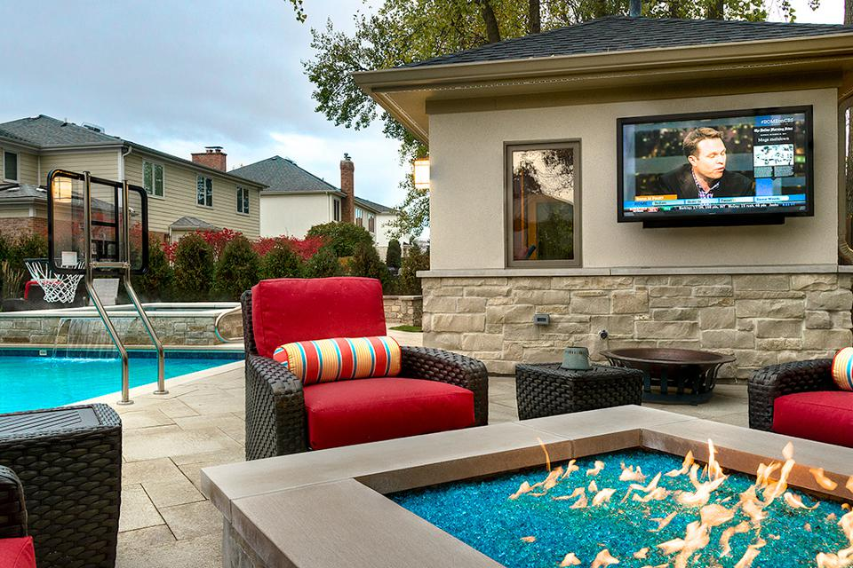 outdoor living room with TV, firepit, pool and basketball hoop.