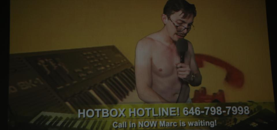 Marc Rebillet is shirtless on a screen with a telephone and keyboard image behind him. There is a hotline number below with the words, ″Call in NOW Marc is waiting!″