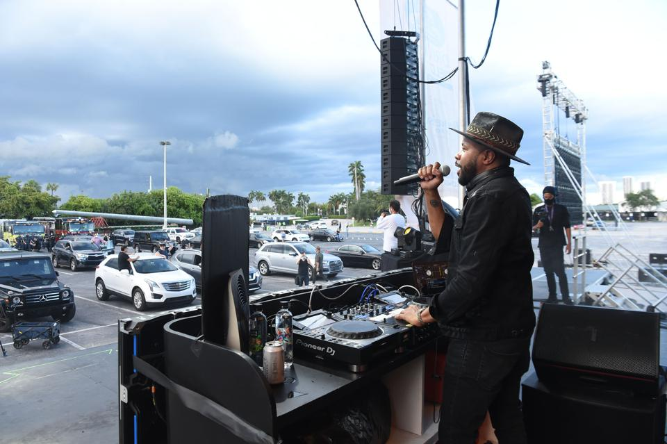 D-Nice holding a microphone talking to the drive-in concert crowd at his DJ station.