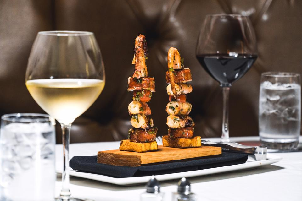 Two glasses of wine and two skewers of scallops.