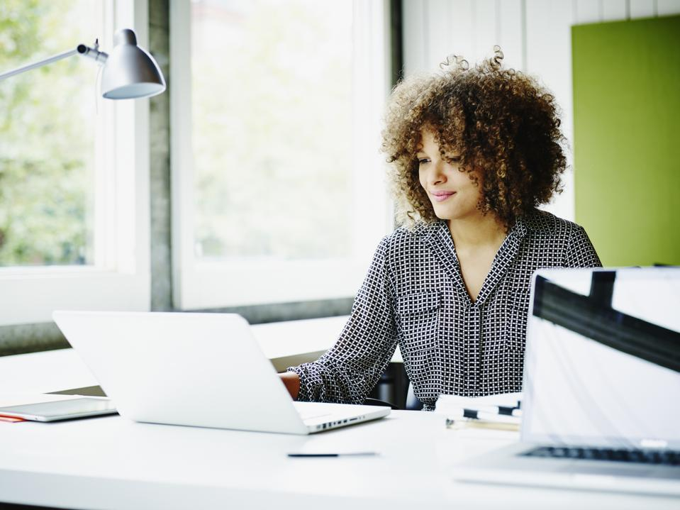 Smiling businesswoman working on project on laptop