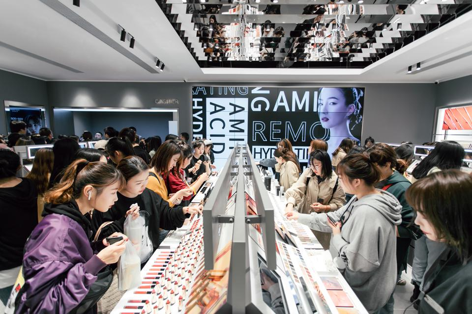 Young Chinese consumers shopping in a busy Perfect Diary store.