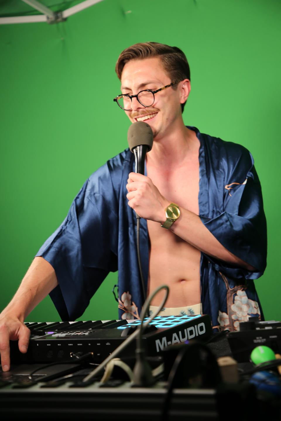 Marc Rebillet is wearing a robe while shirtless in front of his music production station that includes a keyboard and a loop machine.