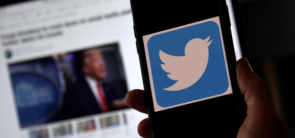 Twitter logo on a mobile phone with an article about President Trump in the background