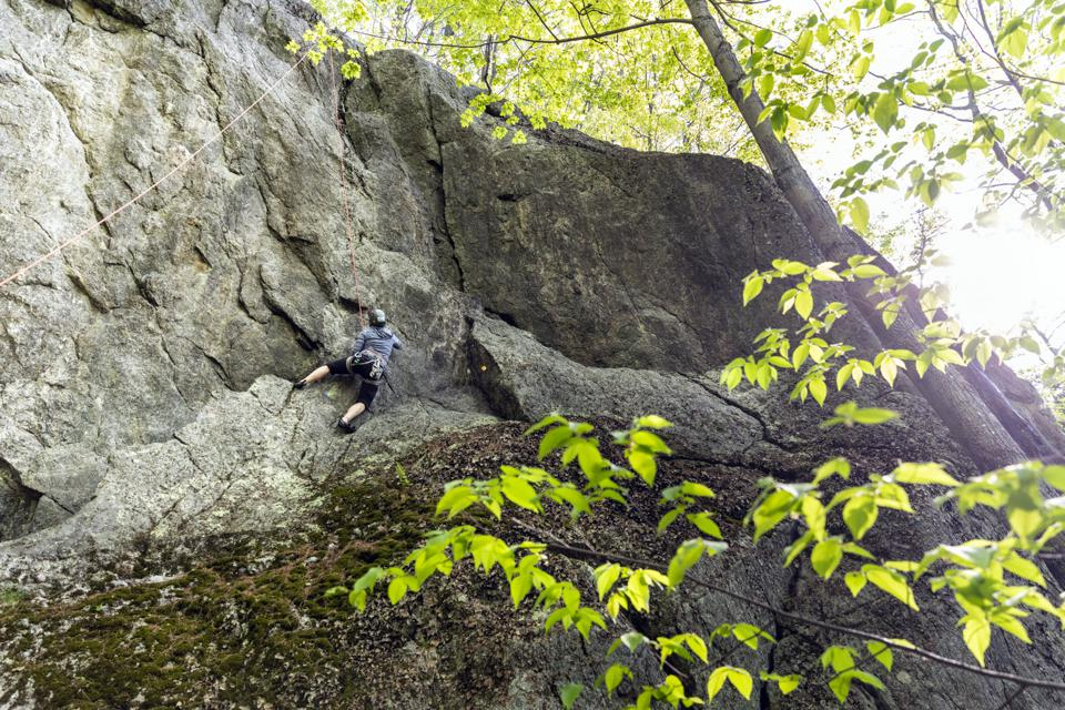 A person doing rock climbing at the Maine property