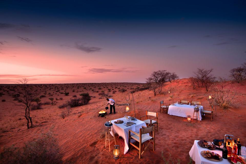 Conservation Africa News - A dinner table set out at twilight looking out at the vast Tswalu Kalahari plains.