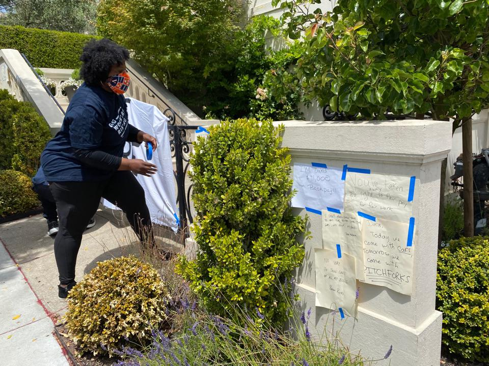 Cherri Murphy, an Uber driver of three years, tapes messages on a pillar outside of Uber CEO Dara Khosrowshahi's home.
