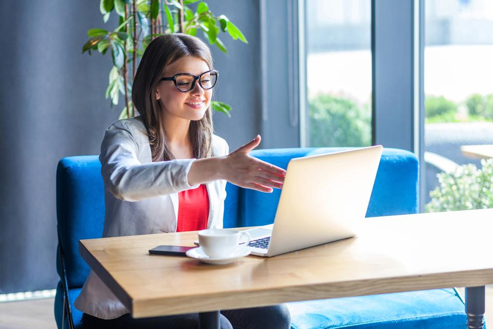 Portrait of happy beautiful stylish young woman in glasses sitting, looking at her laptop screen on video call and giving hand to handshake, toothy smile.