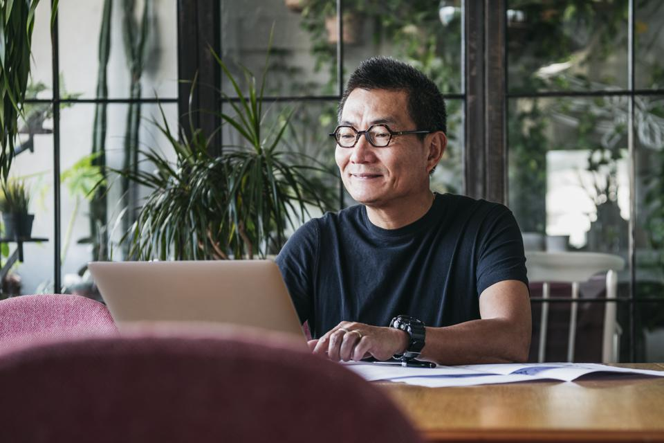 Smiling Chinese man working on laptop at home