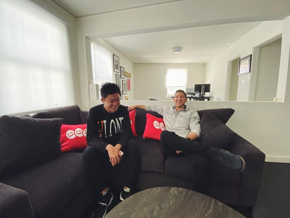 Two men sitting on couch talking and laughing.