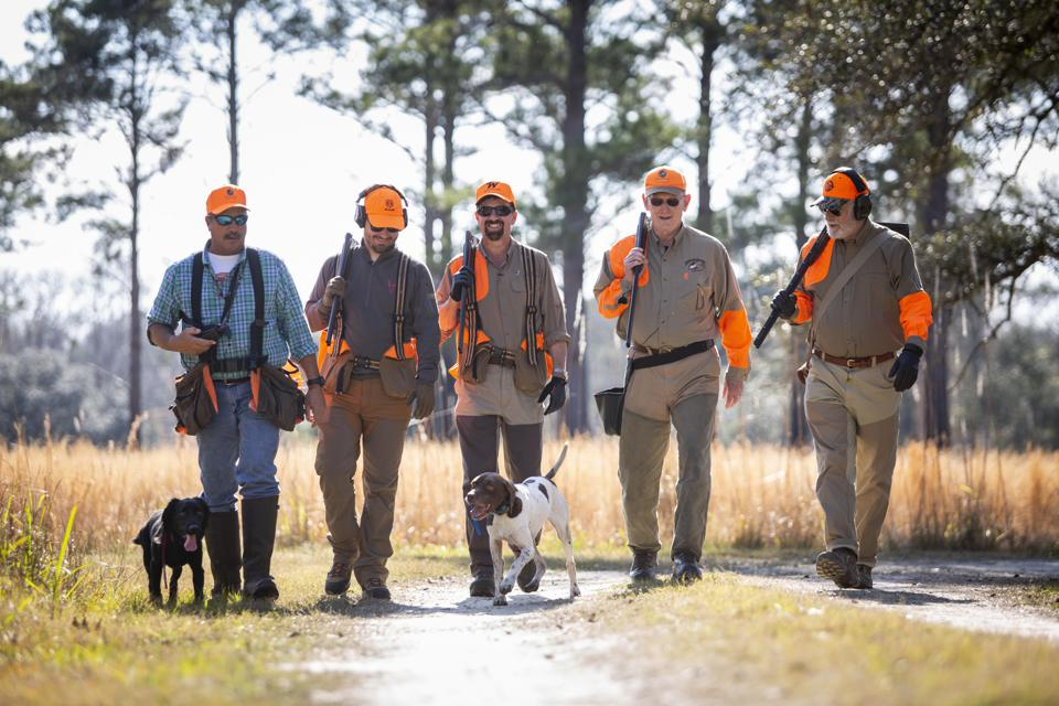 5 men walking with their 2 dogs at Brays Island