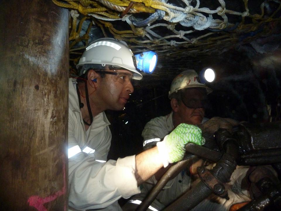 Gautam Mukunda, wearing mine safety equipment, on his hands and knees working a steam drill in the Rustenburg platinum mine.