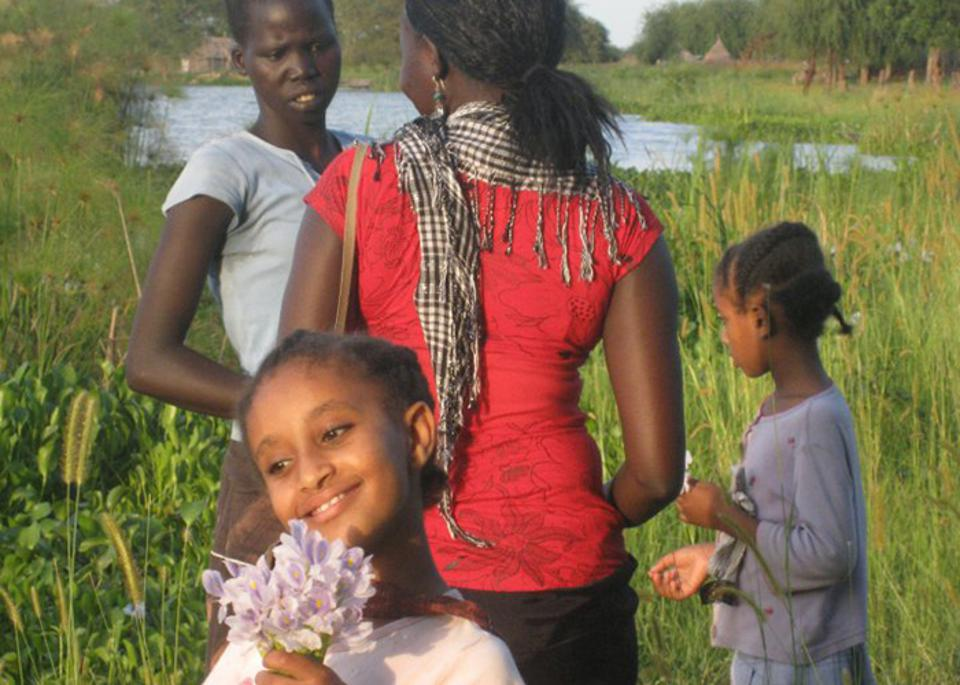 On her return trip to South Sudan in 2009, Deng (in red shirt) picked flowers with girls from the village of Atar, about an hour away by boat from the city of Malakal.