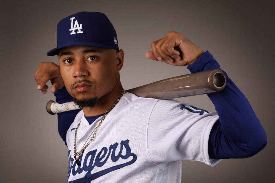 Mookie Betts is wearing a Los Angeles Dodgers' home uniform with a bat on his shoulders.